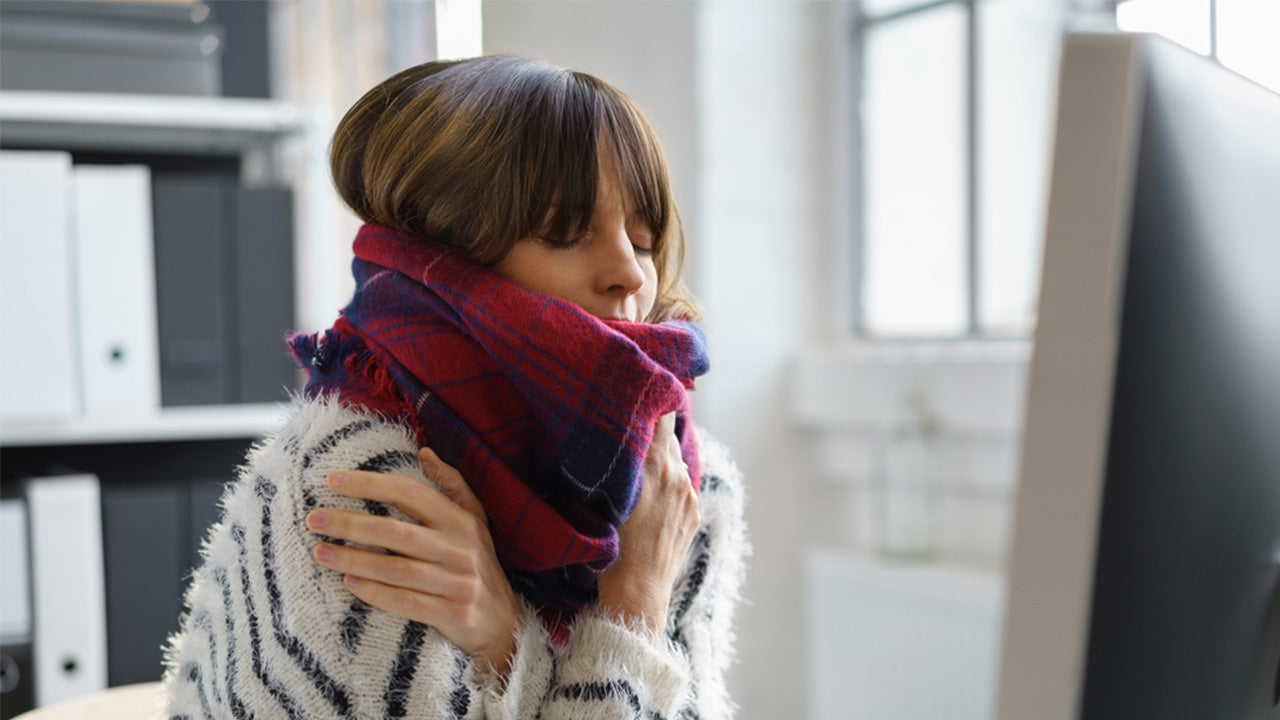 Woman feeling cold wearing sweater, scarf and beanie