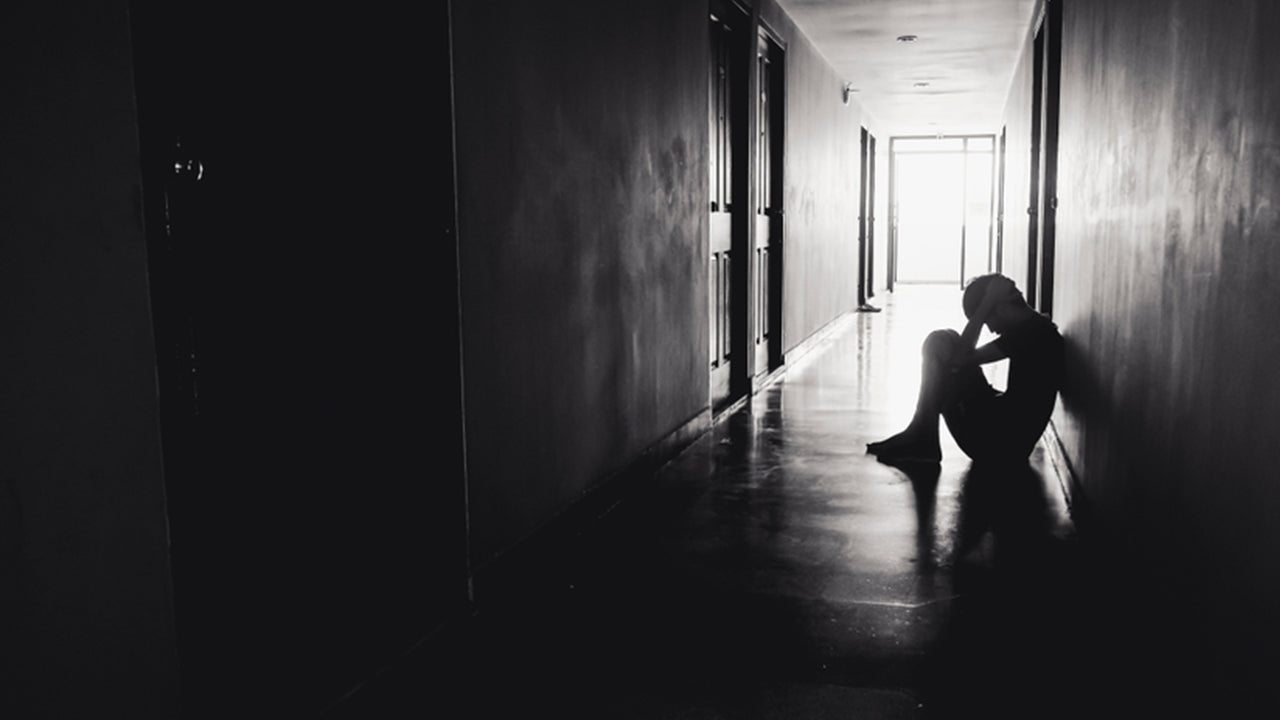 silhouette of a man alone sitting in a hallway black and white
