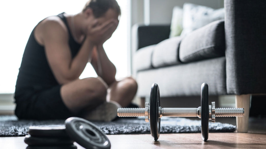dumbbells on the floor and man in the background sitting blurred