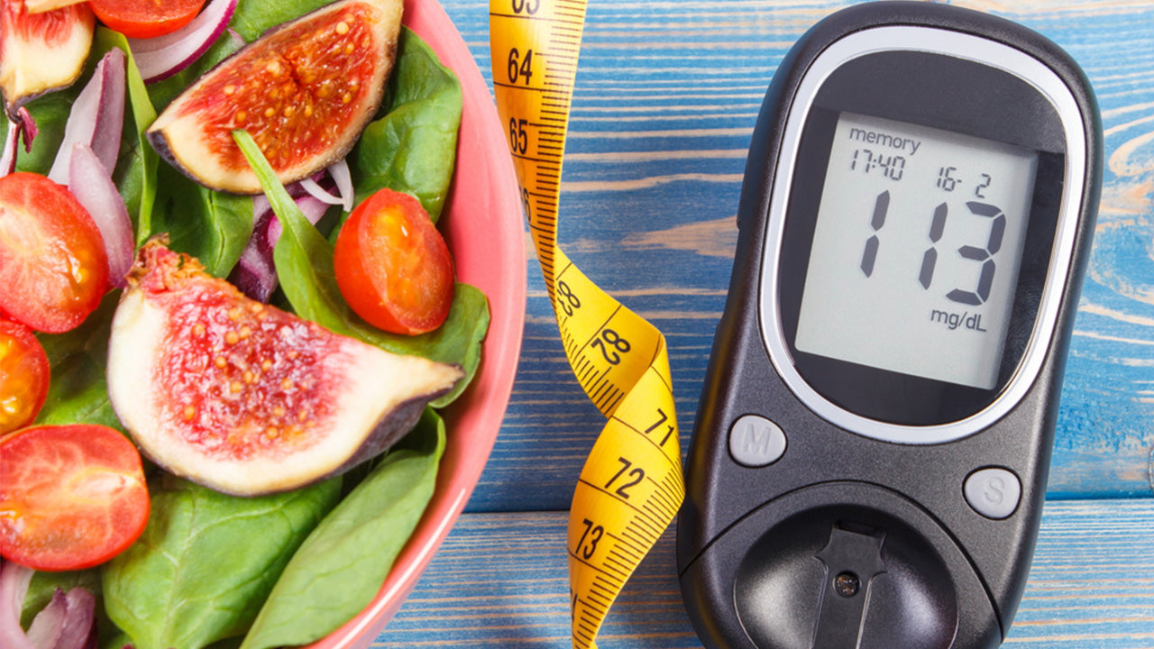 Glucose meter and a bowl of spinach, sliced tomatoes and some fruit