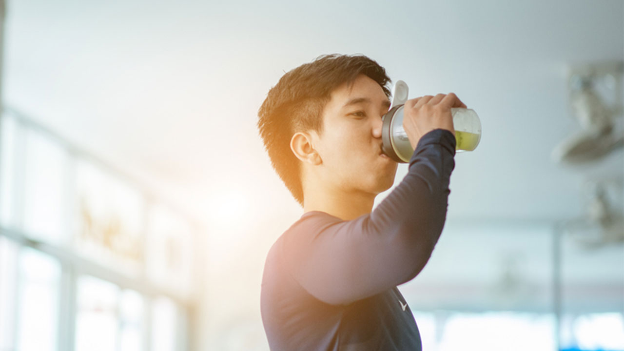 athletic man drinking protein shake