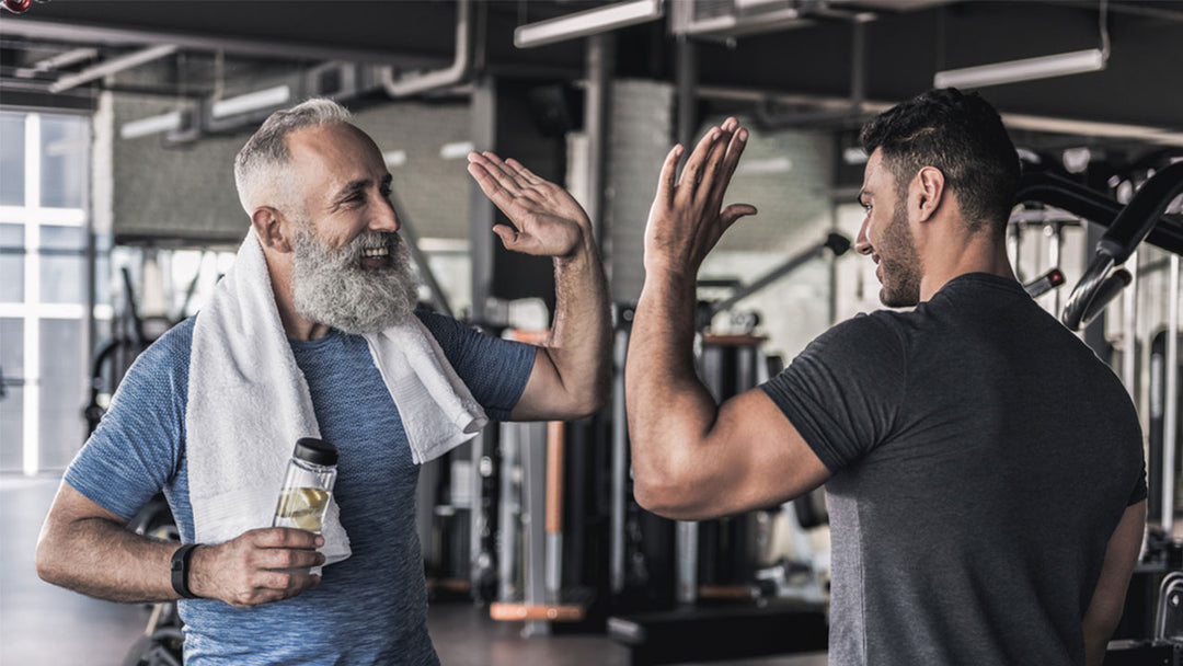 an older adult and a young man at the gym doing high five
