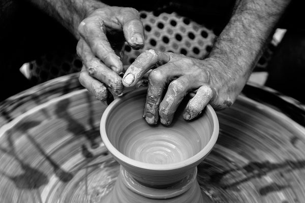 hands spinning pottery to create fair trade home goods