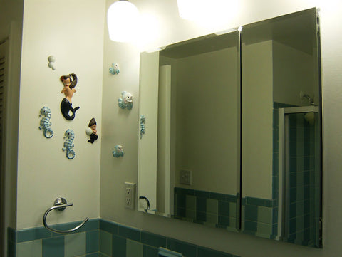 A retro renovation, save the blue bathroom. Barbie K mermaids hang on the wall.