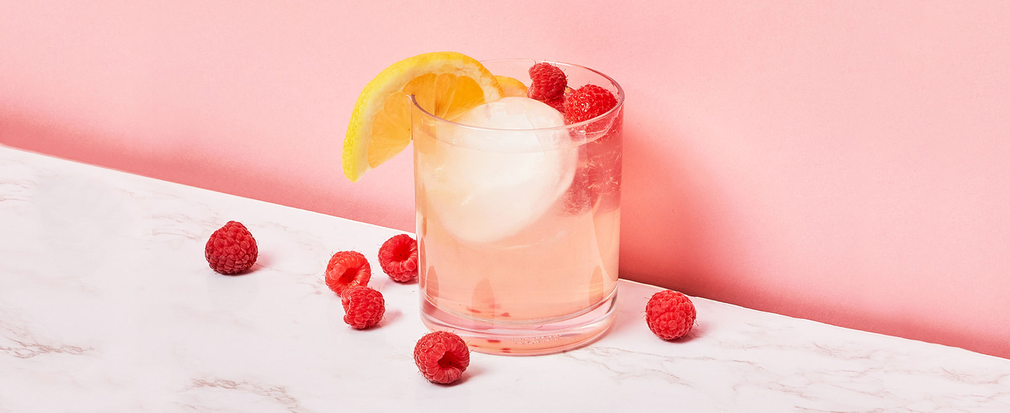 An image of ZOKU's Raspberry Lemonade Cocktail against a pink background.