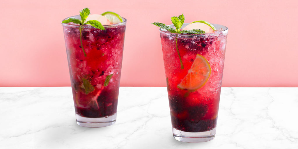 An image of two Blackberry Mojitos against a pink background.
