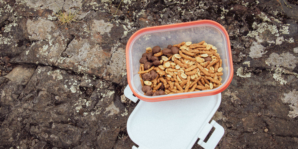 An image of a make ahead camping meal consisting of pretzels, chocolate chips, chocolate covered peanuts, peanuts, cashews, raisins, and banana chips.