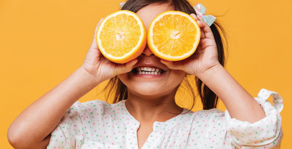 Little girl holding oranges over her eyes and smiling