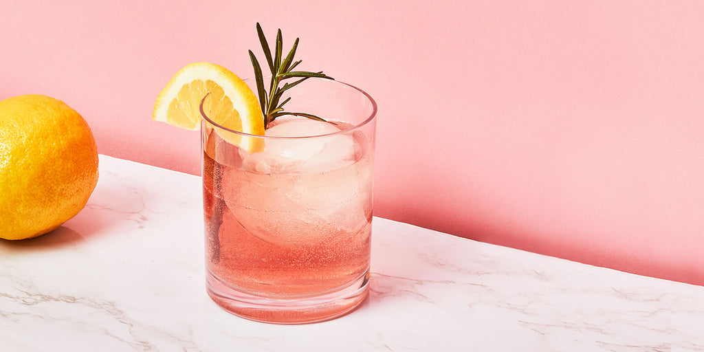 An image of ZOKU's Rosemary Pomegranate Cocktail against a pink background.