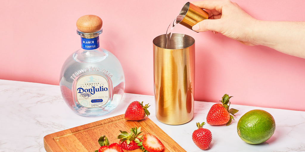 An image of someone pouring Strawberry Margarita ingredients into a cocktail shaker.