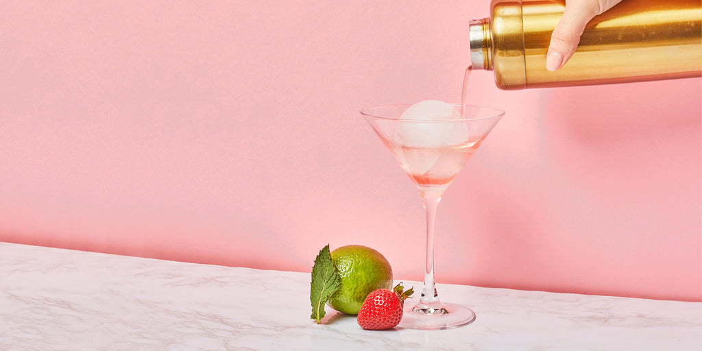 An image of a Strawberry Margarita being strained over an ice ball in a cocktail glass.