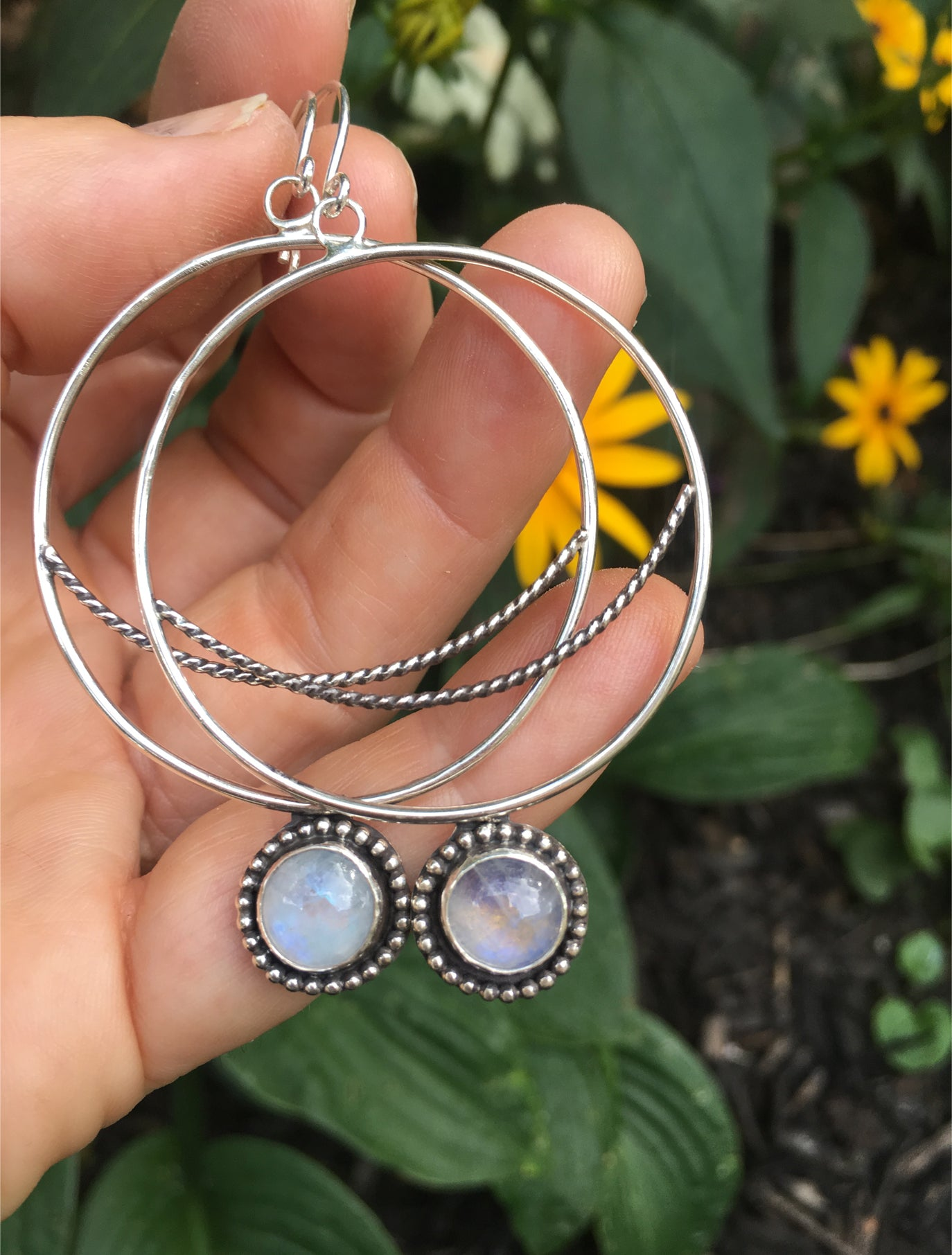 Crescent  Moon Hoops with Rainbow Moonstone Shown in Hand with Flowers in Background