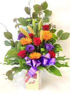 Selection of bright flowers hand tied with chocolates