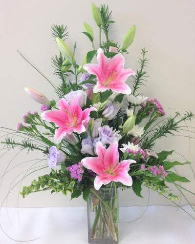 Glass vase with lilly arrangement