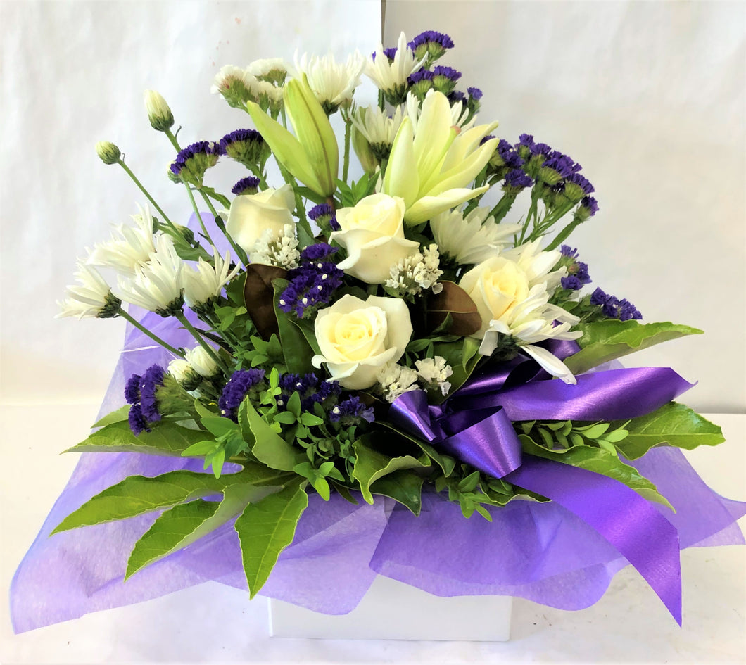 Box Arrangement in purple and white with roses, chrissy's, carnations and lillies