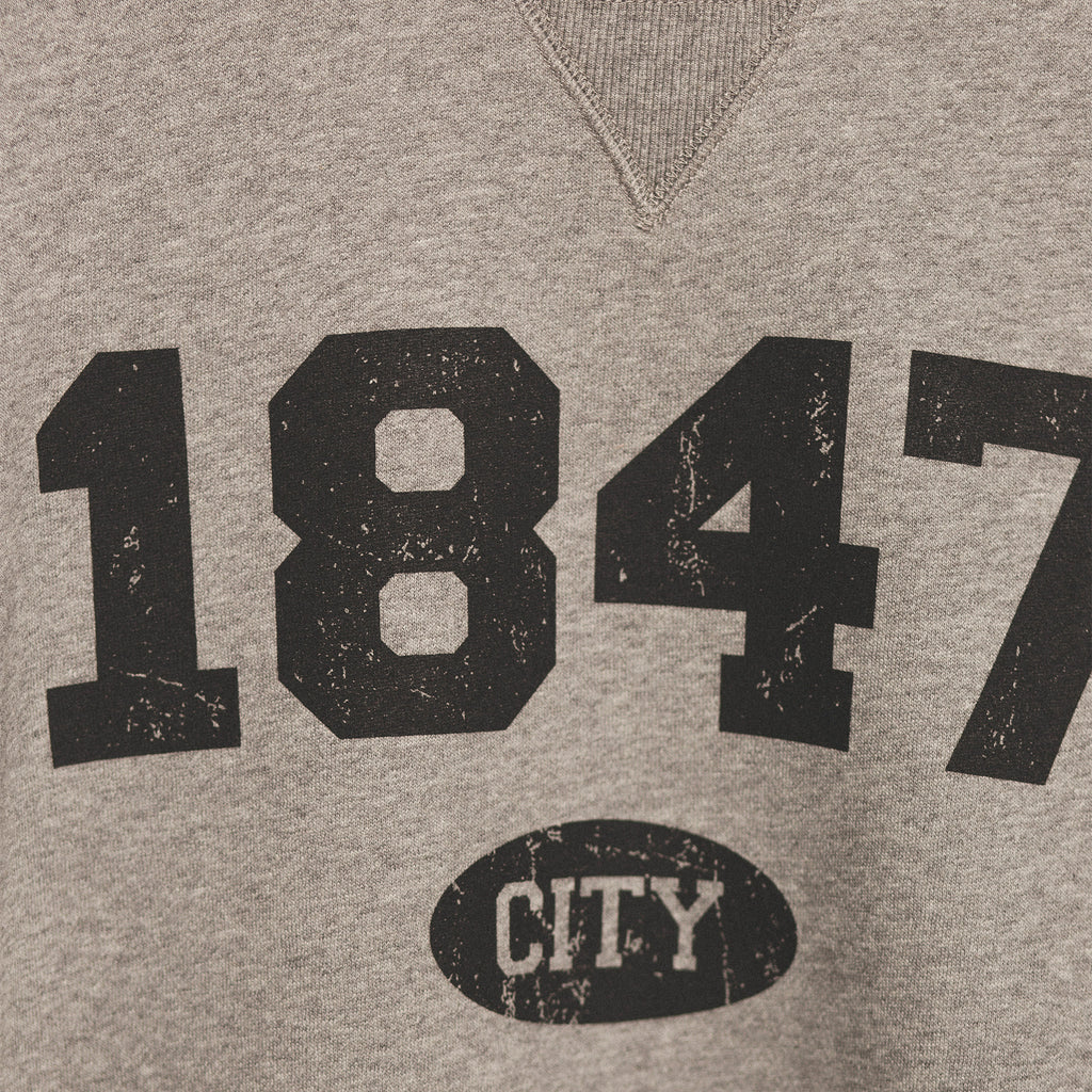 zoomed in image showcasing the screenprinted 1847 established year in black bold lettering with city in small bubble underneath