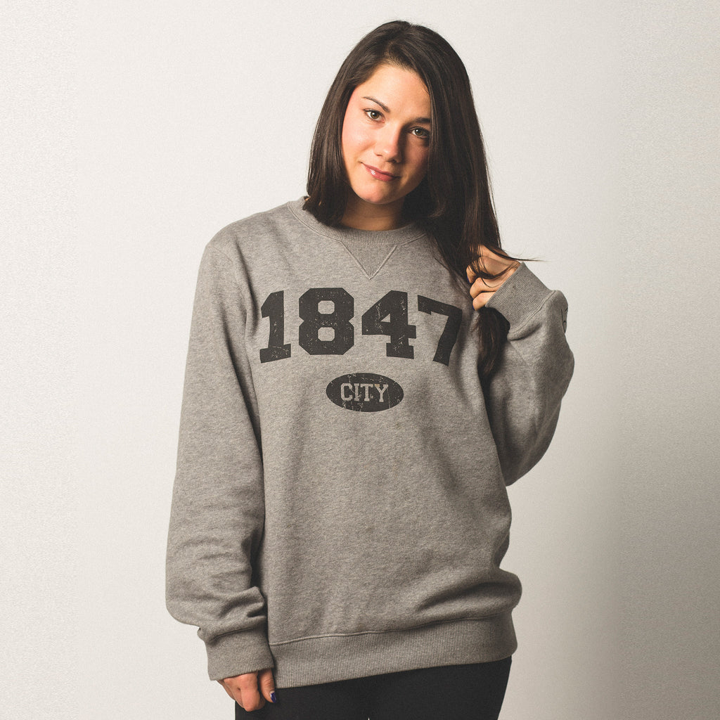 female model with olive skin and black hair wearing a vintage grey crewneck sweatshirt 1847 screen printed on front in black bold lettering city in small bubble underneath size small