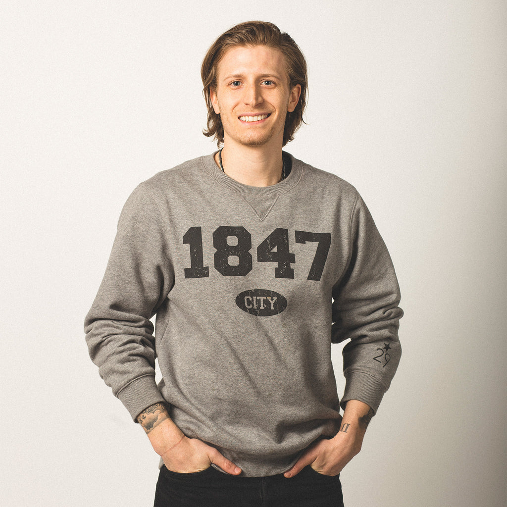 male model caucasian with brown chin length hair wearing crewneck vintage grey sweatshirt featuring bold black lettering of 1847 screen printed on front city in small bubble underneath wearing size medium