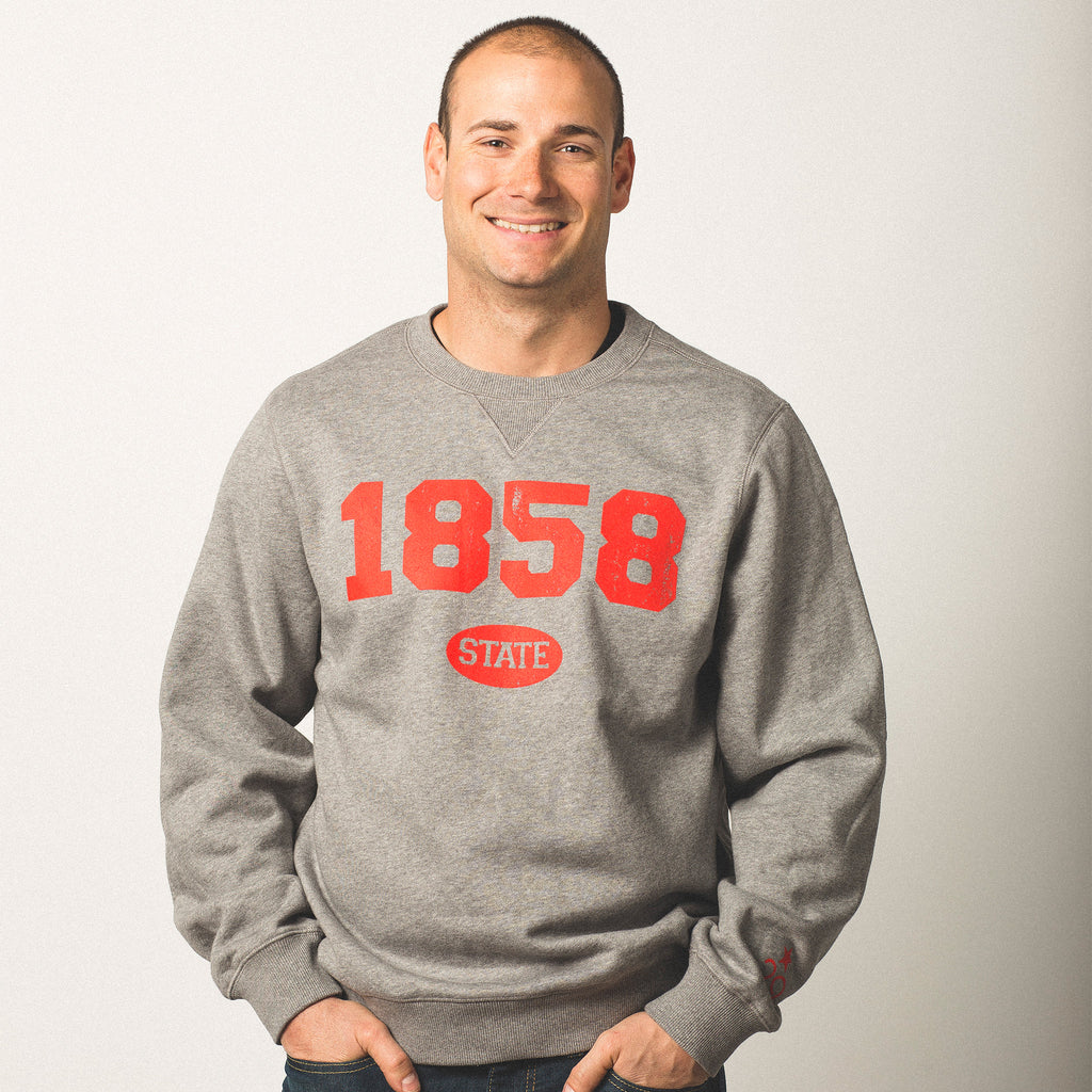 male model caucasian wearing crewneck vintage grey sweatshirt featuring bold bright red lettering of 1858 screen printed on front state in small bubble underneath wearing size medium