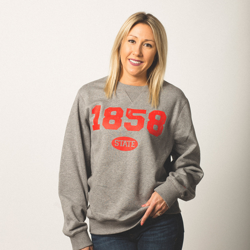 female model caucasian with blonde hair wearing a vintage grey crewneck sweatshirt 1858 screen printed on front in bright red bold lettering state in small bubble underneath size small