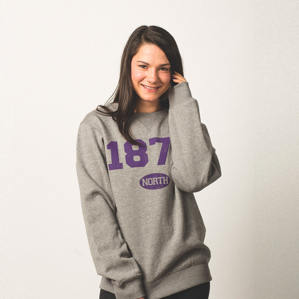 female model with olive skin and black hair wearing a vintage grey crewneck sweatshirt 1876 screen printed on front in purple bold lettering north in small bubble underneath size small