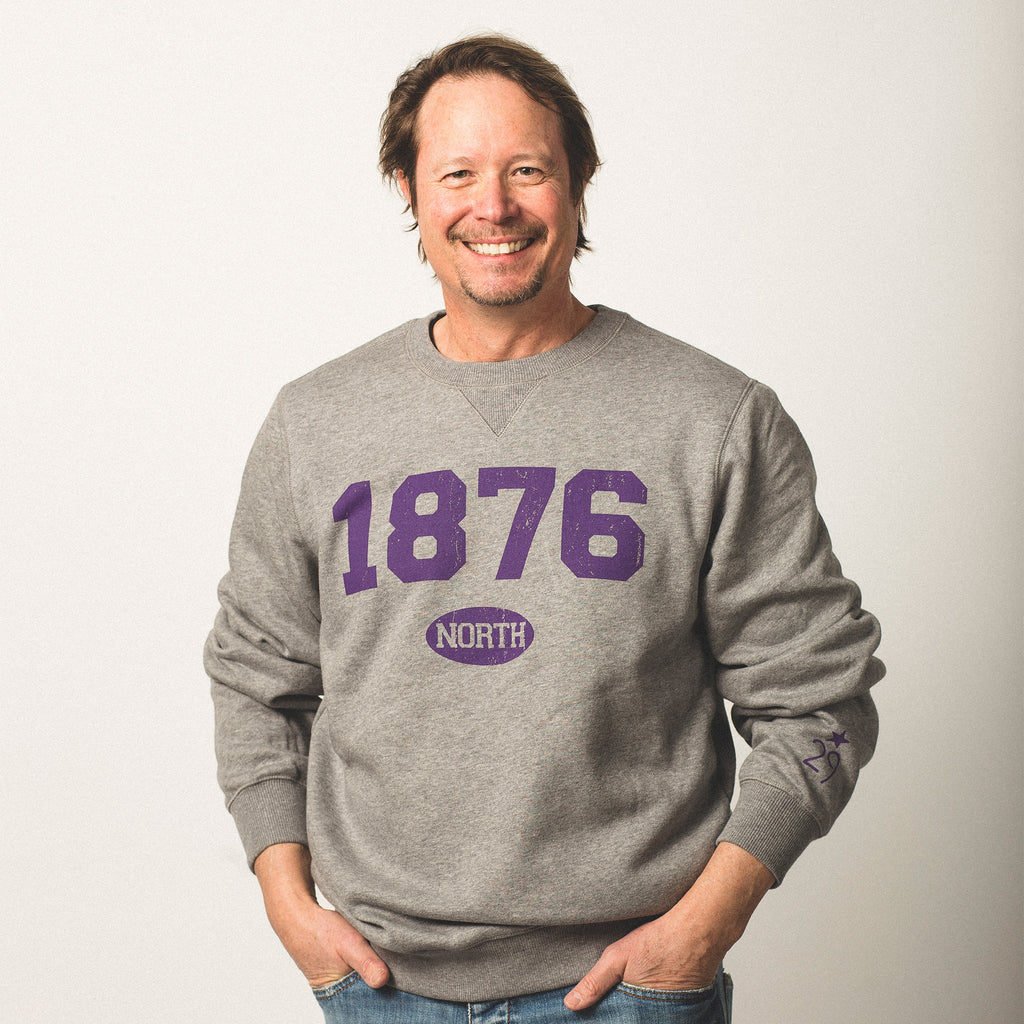 male model caucasian with brown hair wearing crewneck vintage grey sweatshirt featuring bold purple lettering of 1876 screen printed on front north in small bubble underneath wearing size medium