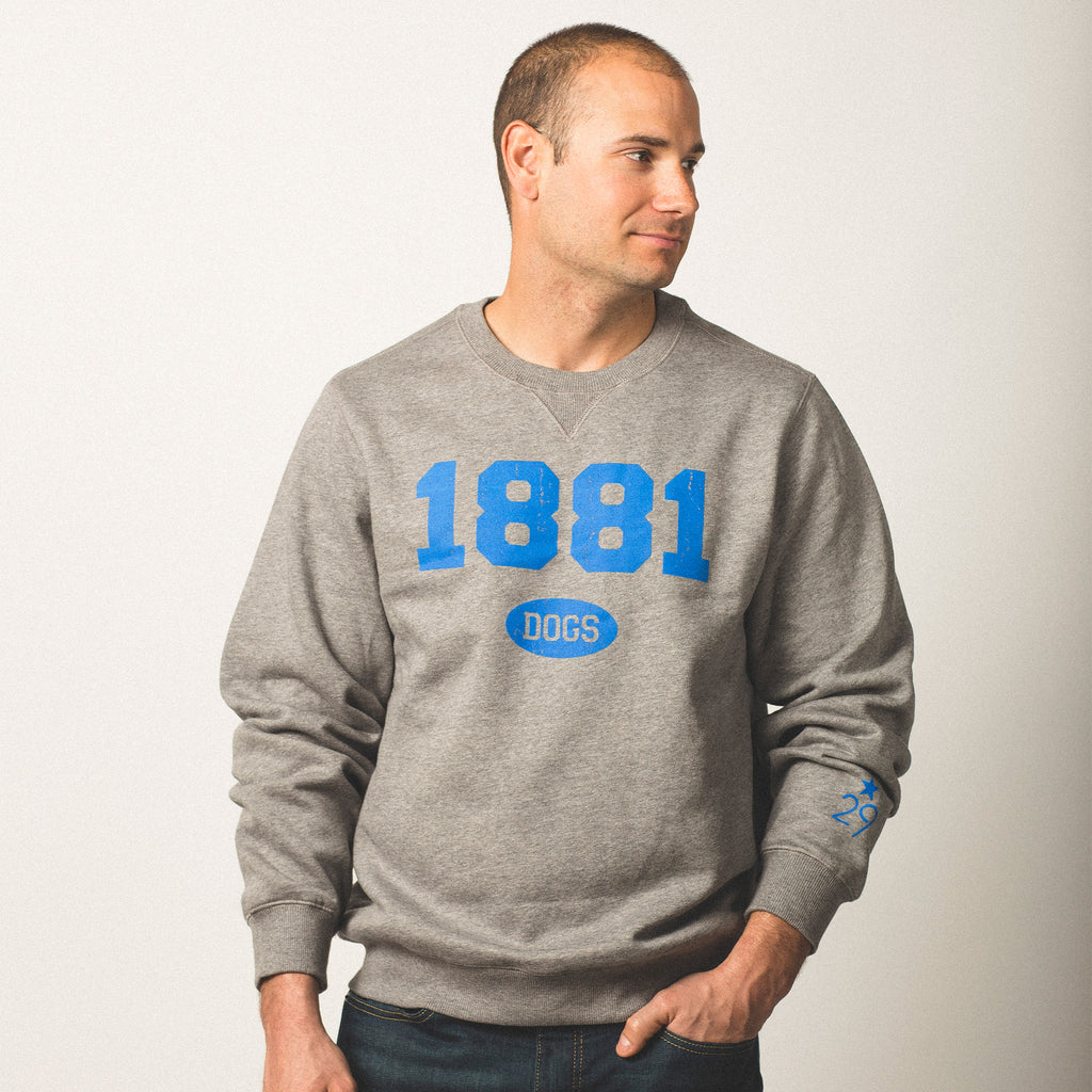 male model caucasian wearing crewneck vintage grey sweatshirt featuring bold blue lettering of 1881 screen printed on front dogs in small bubble underneath wearing size medium