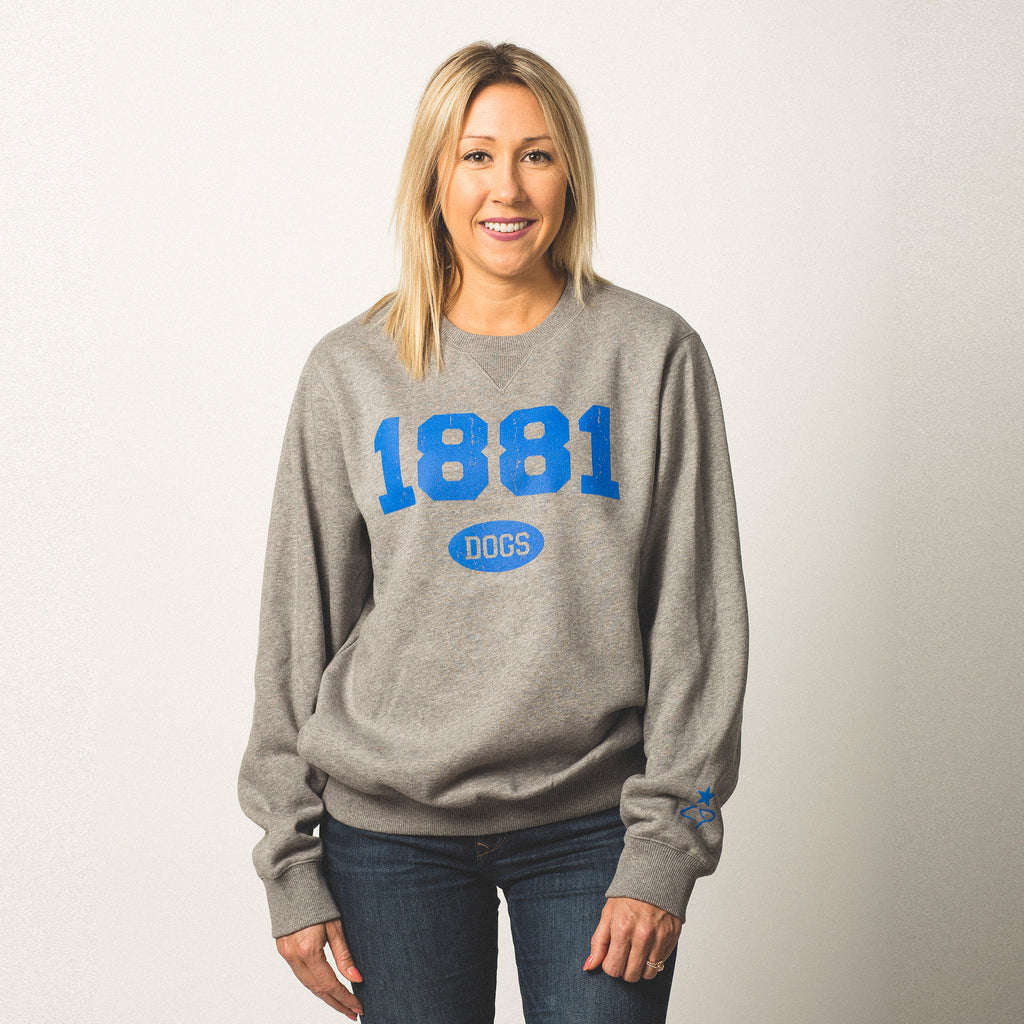 female model caucasian with blonde hair wearing a vintage grey crewneck sweatshirt 1881 screen printed on front in blue bold lettering dogs in small bubble underneath size small