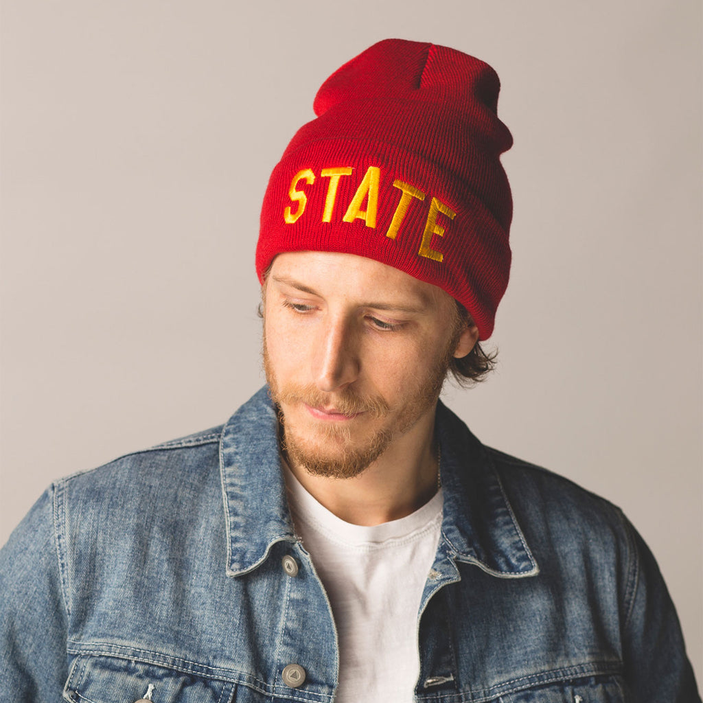 male model with short beard and mustache wearing red beanie with folded cuff state embroidered in gold lettering