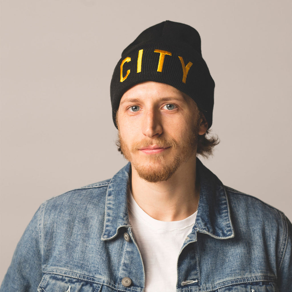 blonde haired blue eyed male model wearing black beanie with folding cuff in cuff city embroidered in gold