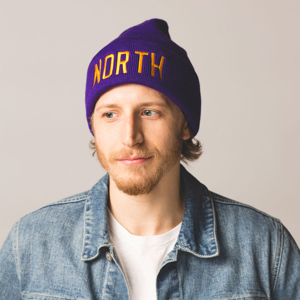 male model with short beard and mustache wearing a purple beanie with a folded cuff north embroidered in gold on front
