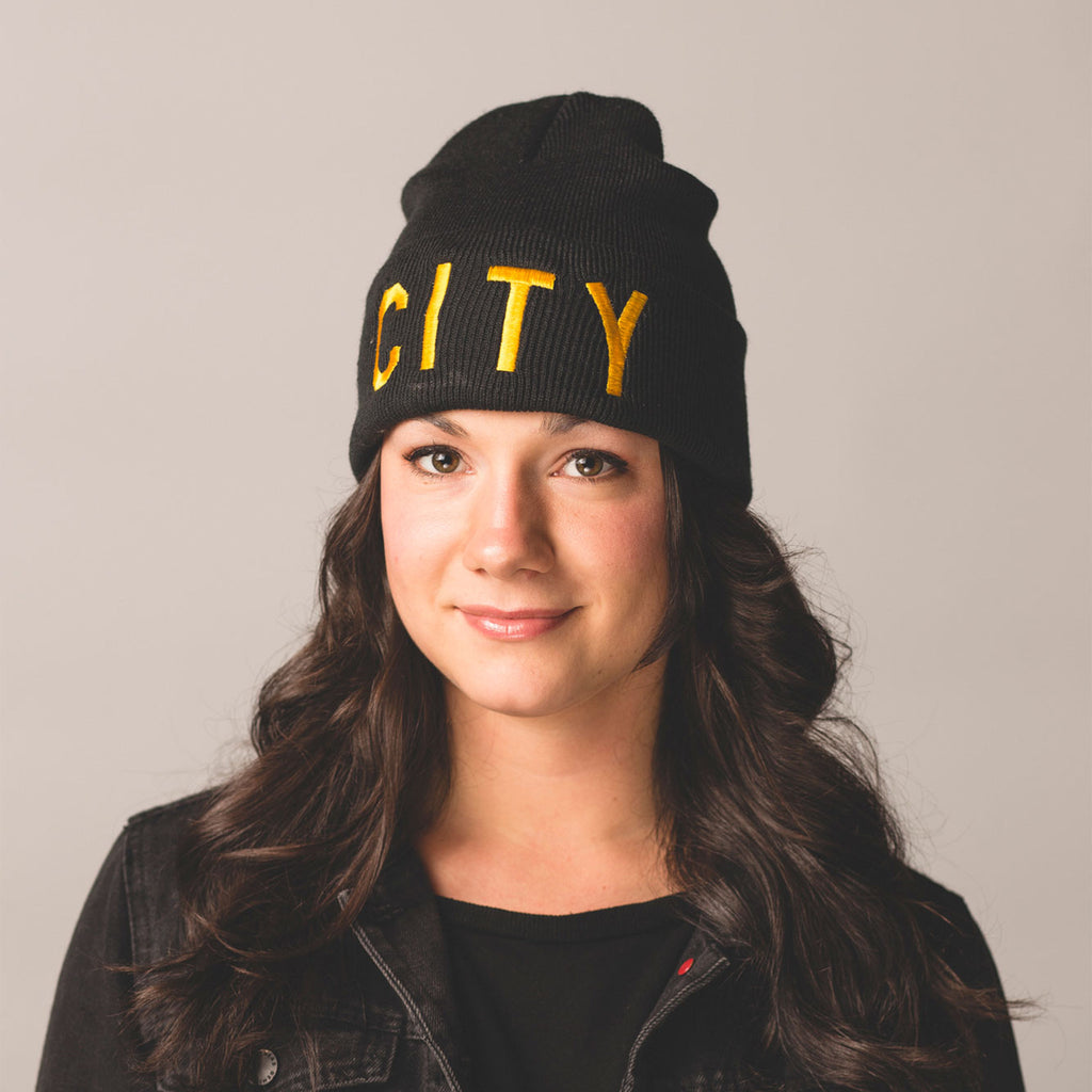 black haired model brown eyes smiling wearing black beanie with folding cuff city in gold bold lettering