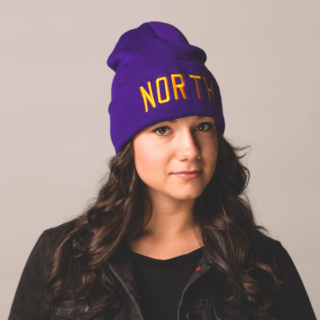 female model with black hair wearing a purple beanie with folded cuff north embroidered in gold on front