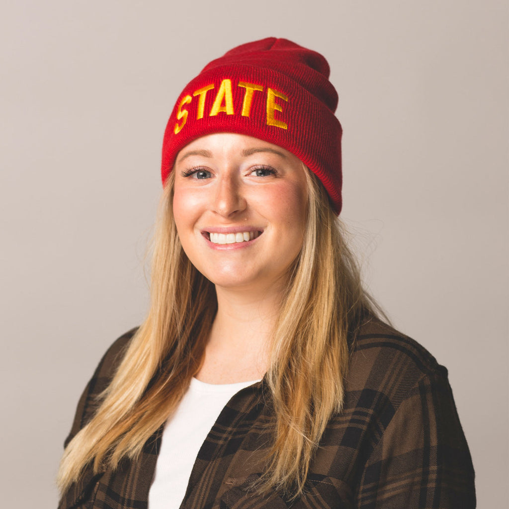 blonde long haired model smiling wearing red beanie with folded cuff state embroidered on front in gold