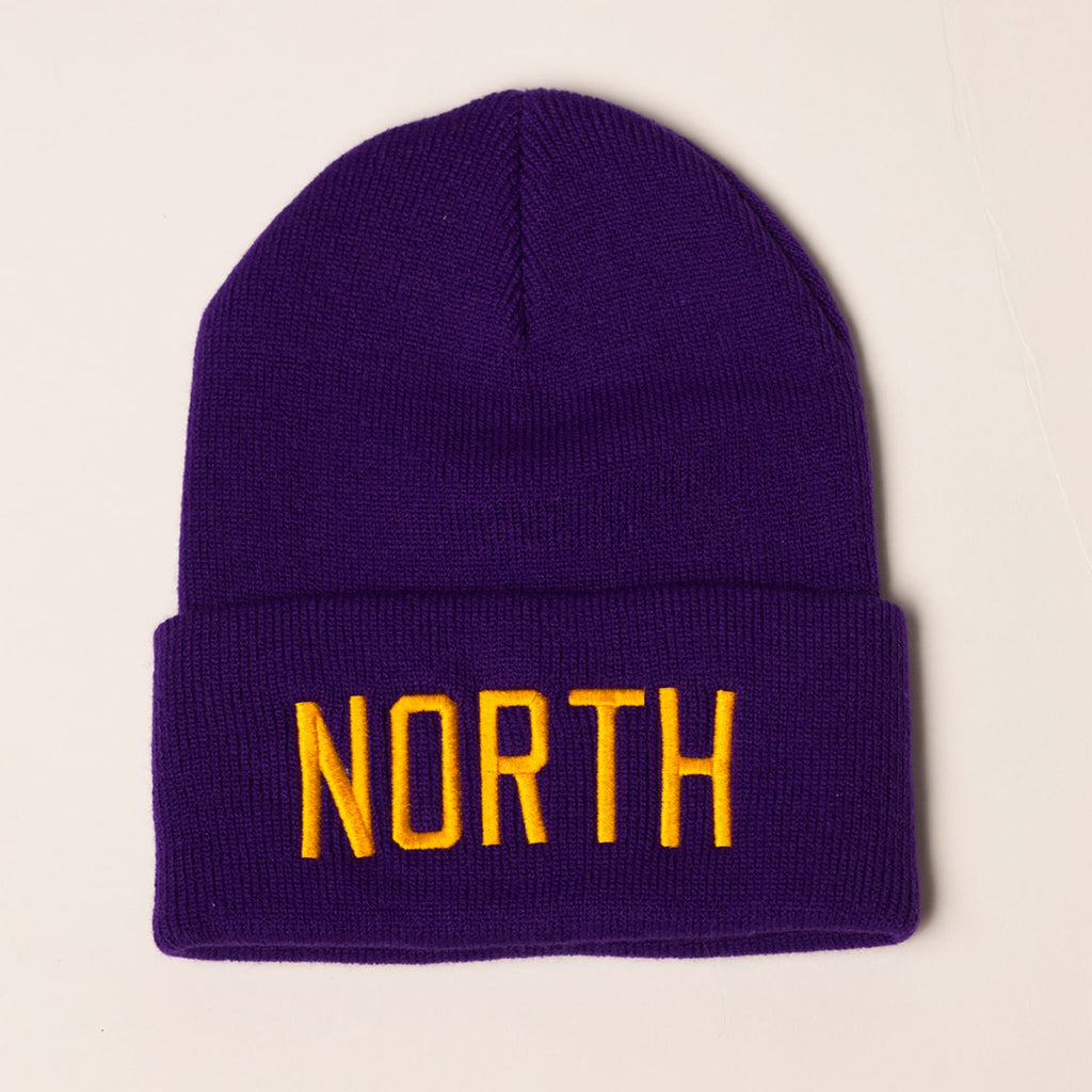 purple beanie with folding cuff north embroidered in gold on front