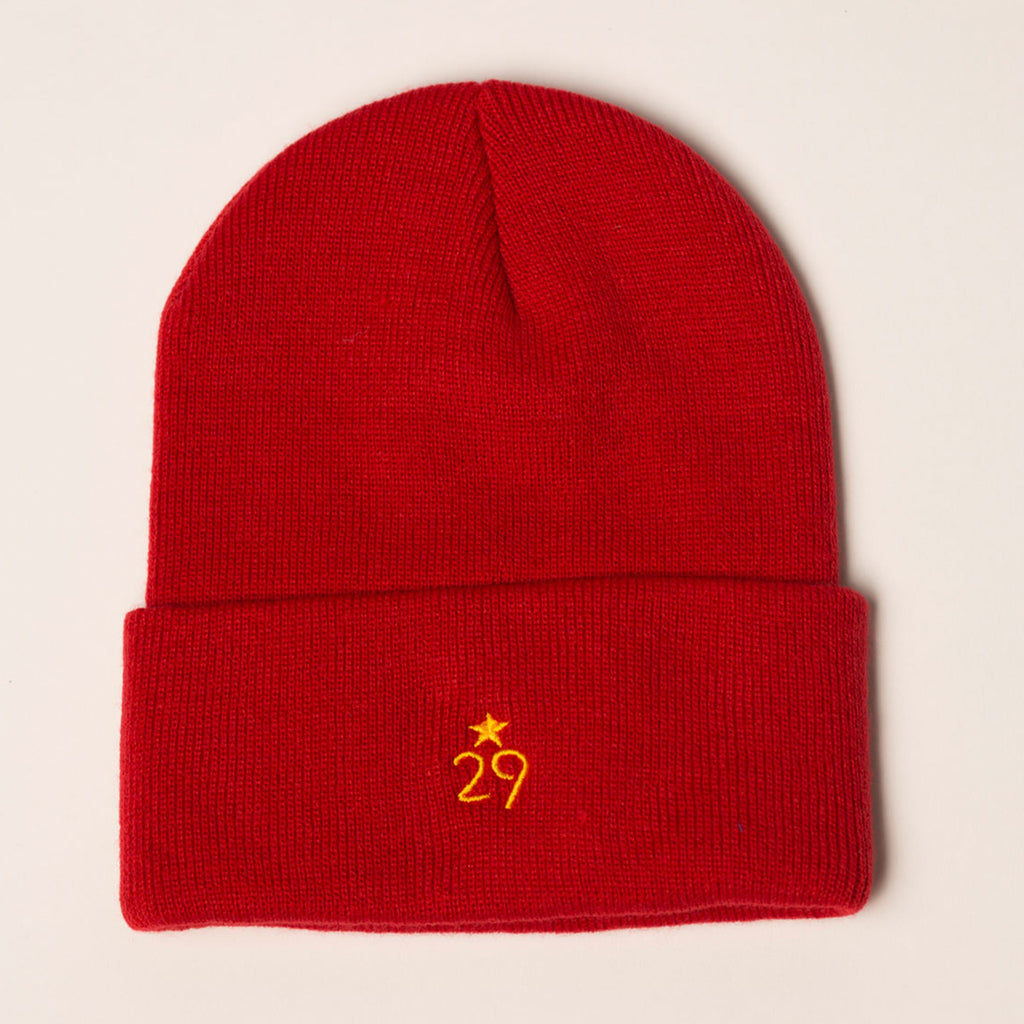 red beanie with folding cuff logo in gold centered on back
