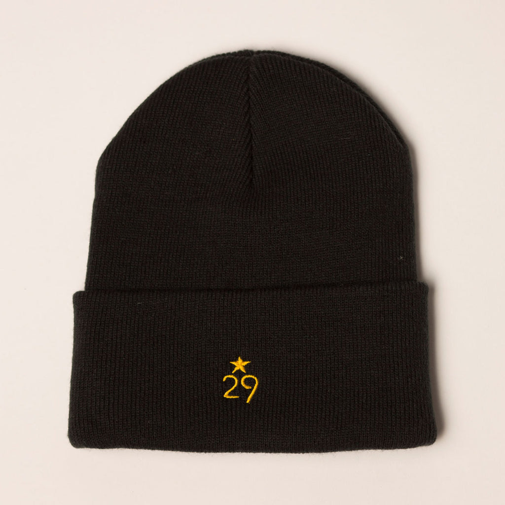 black beanie folding cuff with logo centered on back in gold