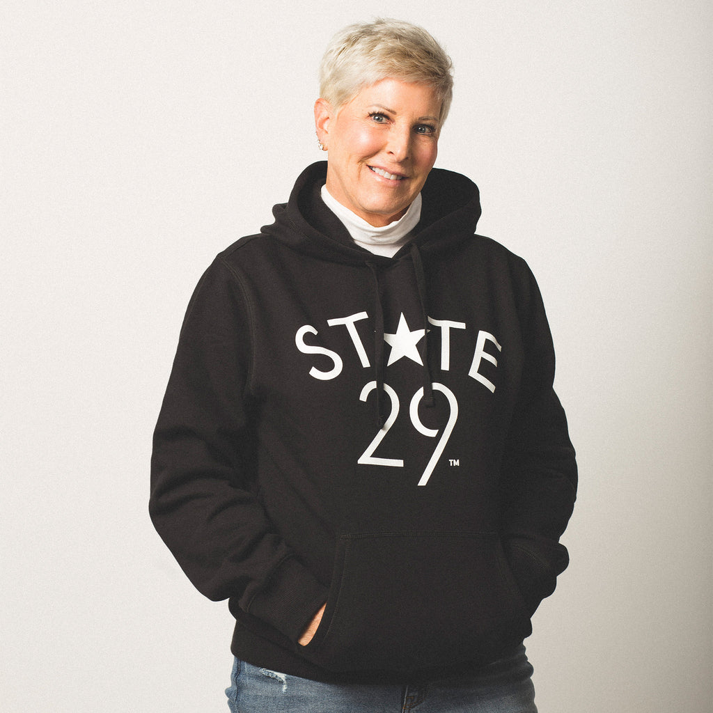 female model short blonde hair wearing a black pullover hooded sweatshirt featuring the 29th State Apparel logo trademarked in white on front above pouch