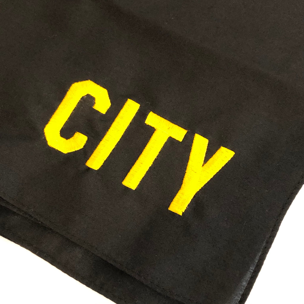 closeup of city embroidered in gold in corner of black bandana