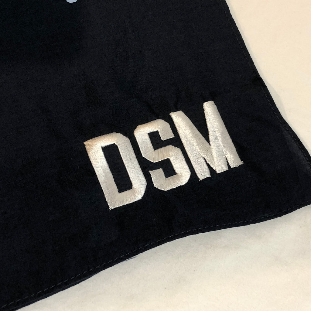 closeup of DSM embroidered in white in corner of navy bandana