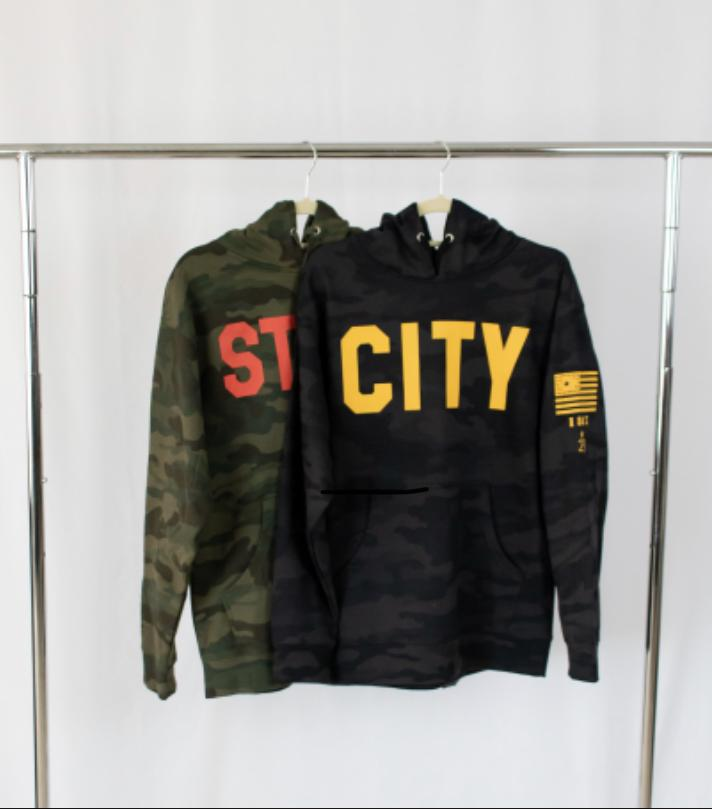 two hooded sweatshirts hanging from a silver rack a black camoflauge military inspired sweatshirts hangs first city in gold on front in bold details also in gold on left sleeve