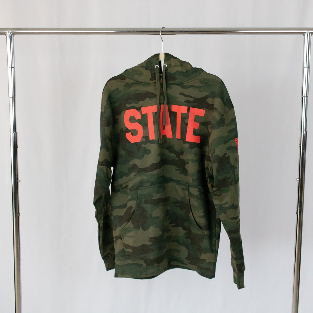 a hanging military green camo print hooded sweatshirt with state in red printed on front
