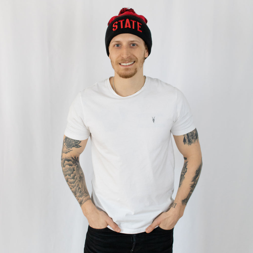 tattooed young man smiling in a white tee shirt wearing a two-tone black and red striped beanie state in red on front fold
