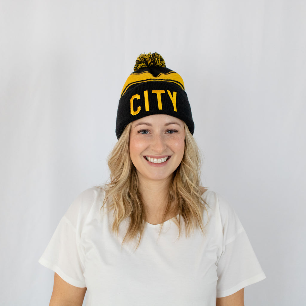 blonde haired young woman in white tee with black and gold striped beanie and a pom on top city embroidered on front center