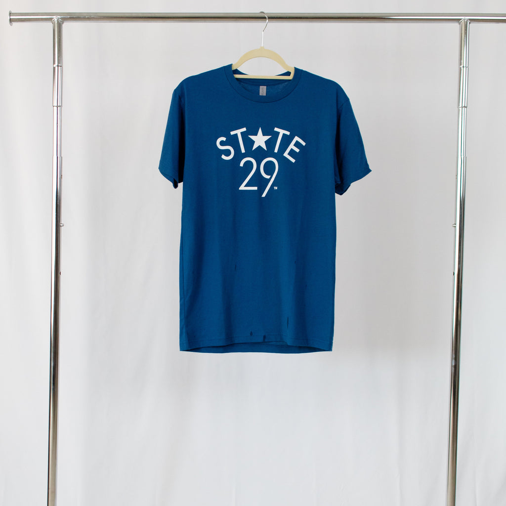 cool blue tee shirt with 29th state apparel logo in white centered on front hanging from silver rack