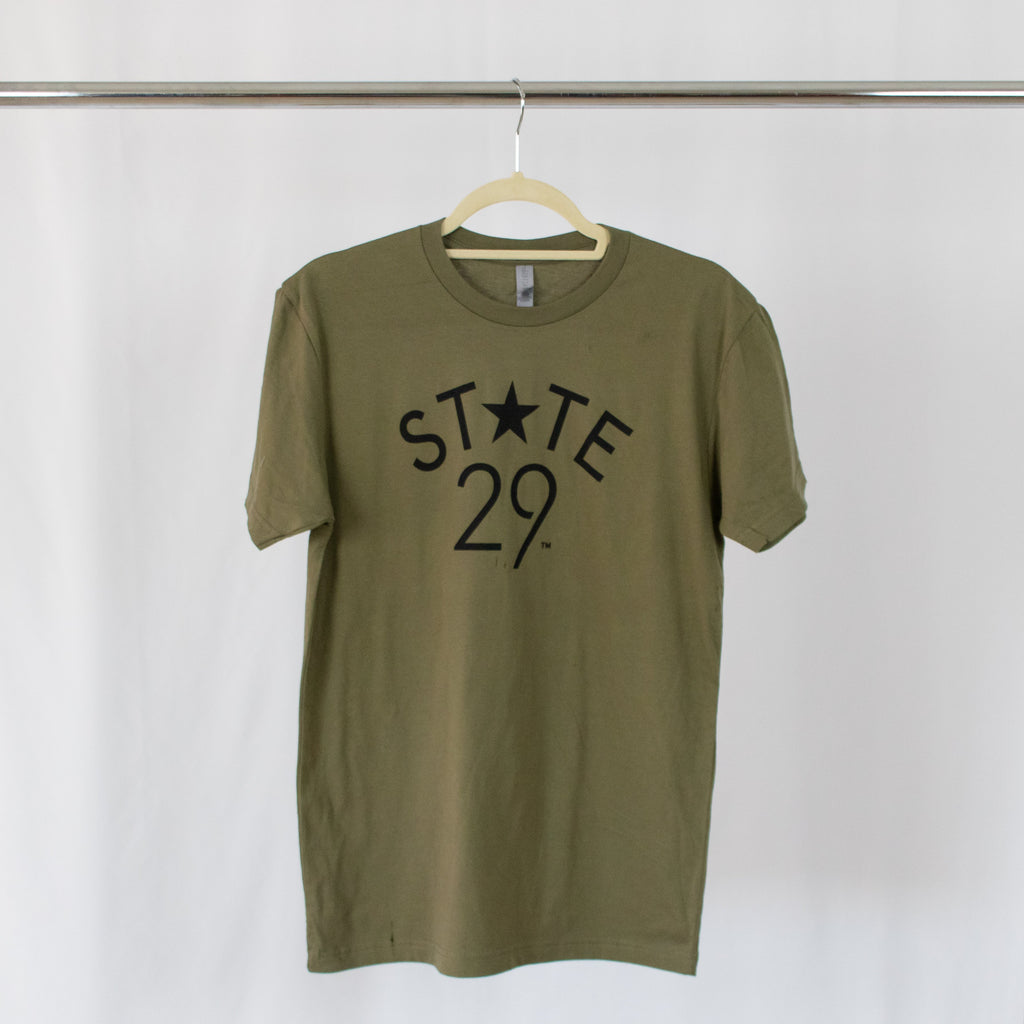 olive green tee shirt with black 29th state apparel logo on front center hanging from silver rack