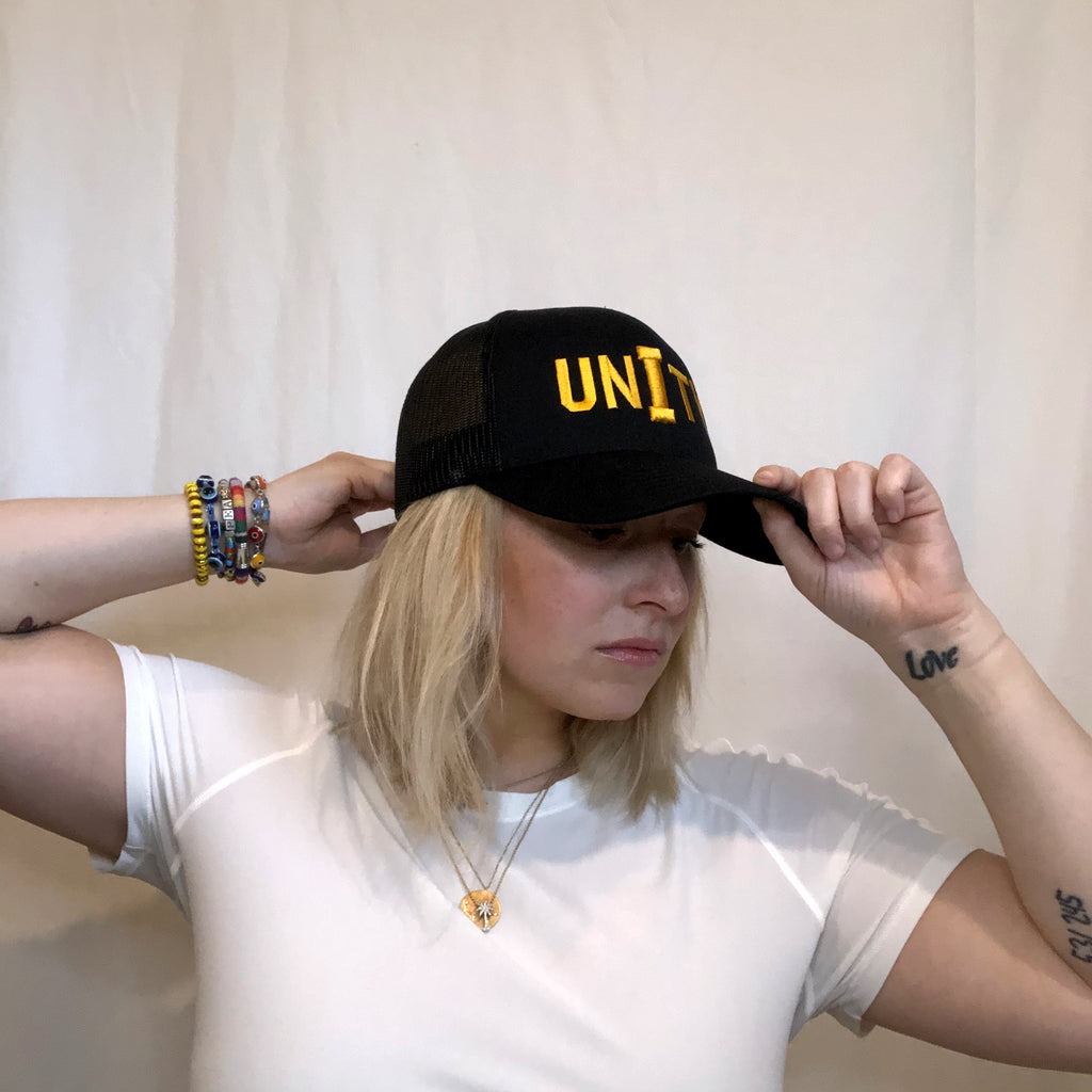 young women with blonde hair reaching for the front bill and back of an all black hat on her head unity embroidered in gold on front