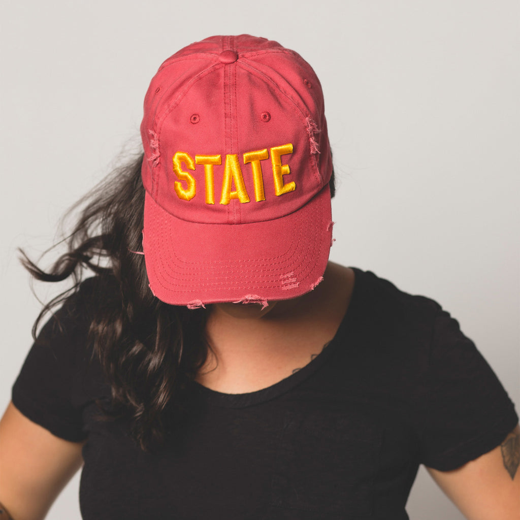 front view on model of red STATE Distressed Baseball Hat