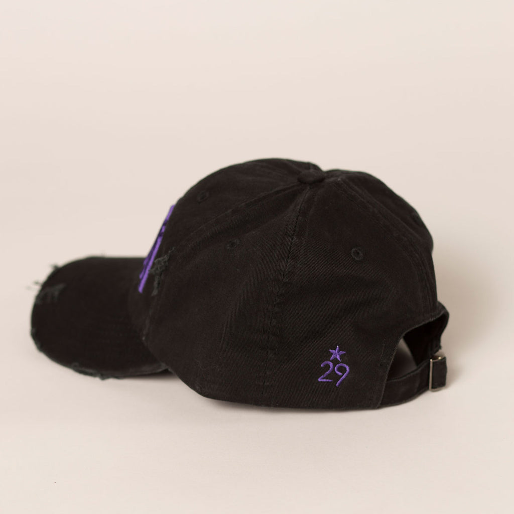 back side view black distressed baseball hat small purple logo near slide closure