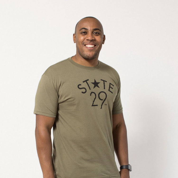 tall dark young man wearing an olive green tee with the 29th state apparel logo on the front in black